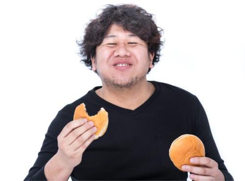 満面の笑みでハンバーガーを食べる男性