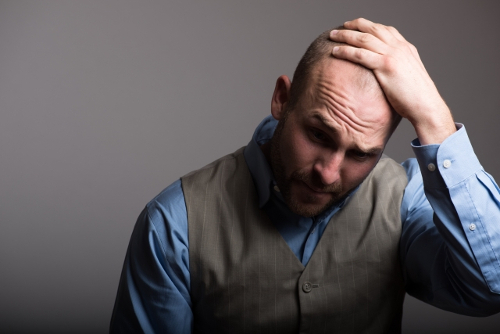 頭を抱えるスキンヘッドの男性