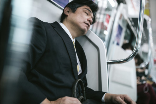 電車で居眠りするお父さん